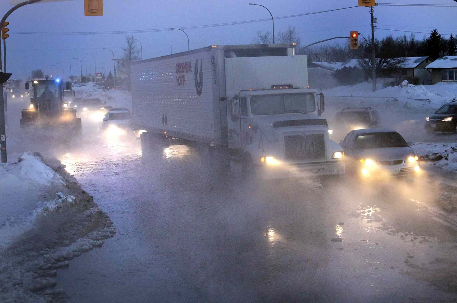 Traffic moves slowly through the water from a large water main break on southbound lanes of Route 90 at Selkirk Avenue on a -25C Tuesday morning. Water main breaks have consistently plagued city workers and commuters this winter. (Wayne Glowacki / Winnipeg Free Press)