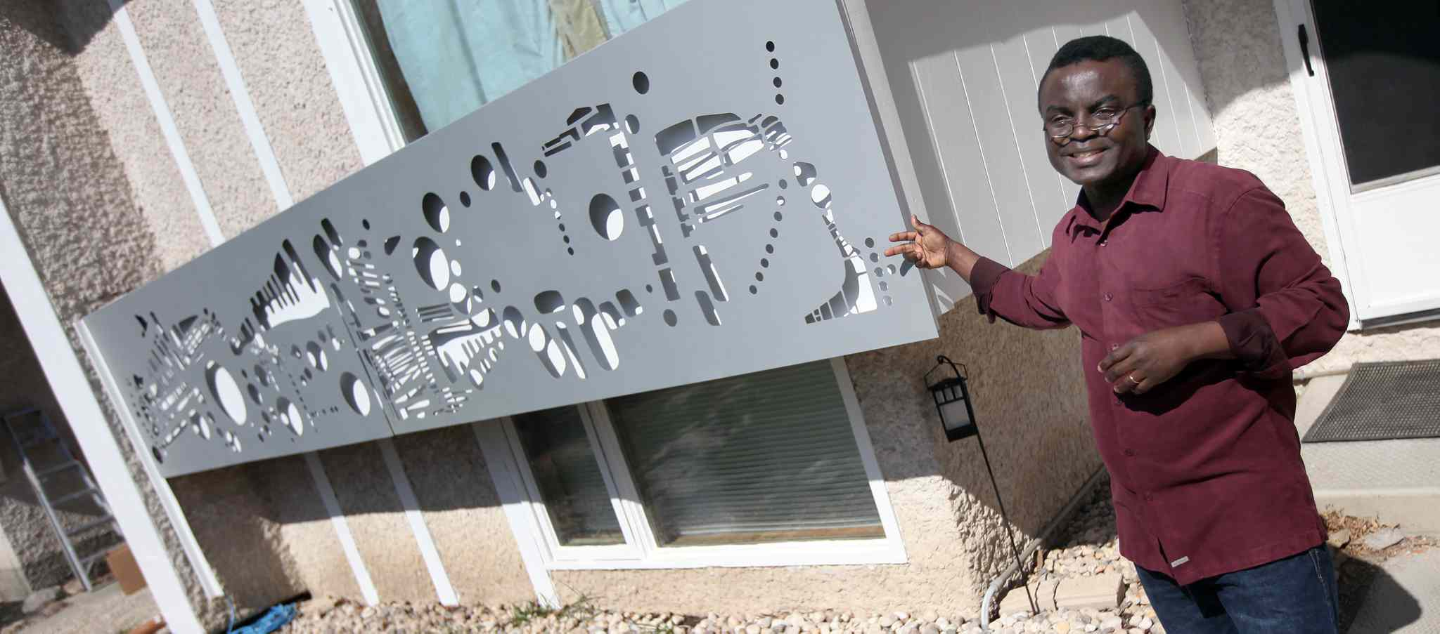 Artist Yisa Akinbolaji with a metal mural adorning his St. Vital home. The Yoruba are a southwest African tribe mainly from Nigeria, Benin, Burkina Faso and Togo. Yoruba culture and art are being celebrated in YorubaFest.