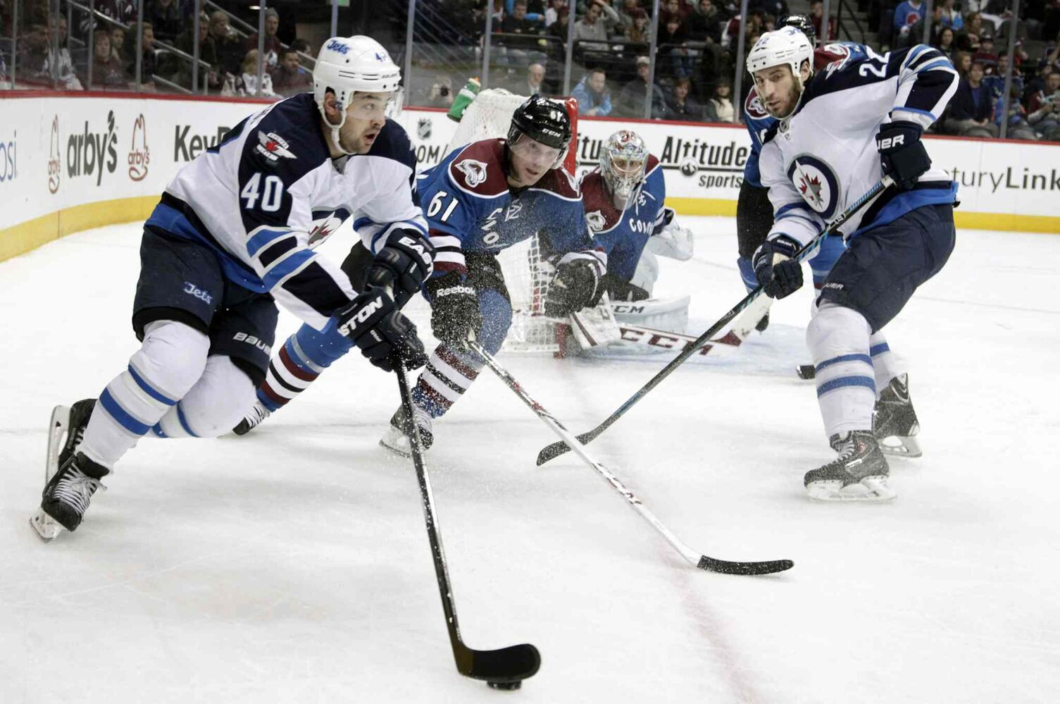 Winnipeg Jets winger Devin Setoguchi (left) carries the puck along the boards as Colorado Avalanche defenceman Andre Benoit (61) gives chase and Jets winger Chris Thorburn (right) and Avalanche goalie Semyon Varlamov watch. (Joe Mahoney / The Associated Press)