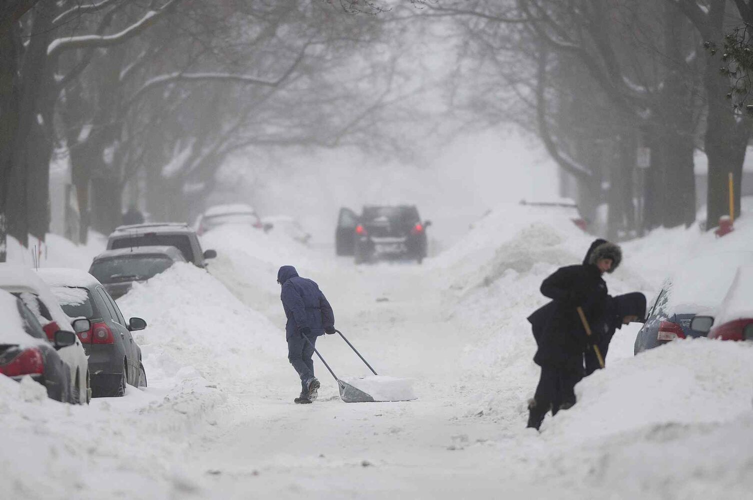 People clear snow from around their cars on a street in Montreal on Sunday. (Graham Hughes / The Canadian Press)