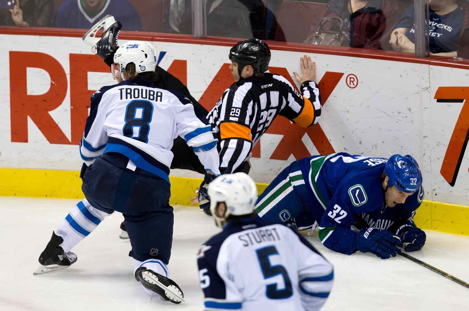 Referee Ian Walsh (centre) is knocked to the ice after Winnipeg Jets defenceman Jacob Trouba (left) and Vancouver Canucks' Dale Weise collided during the second period. (DARRYL DYCK / THE CANADIAN PRESS)