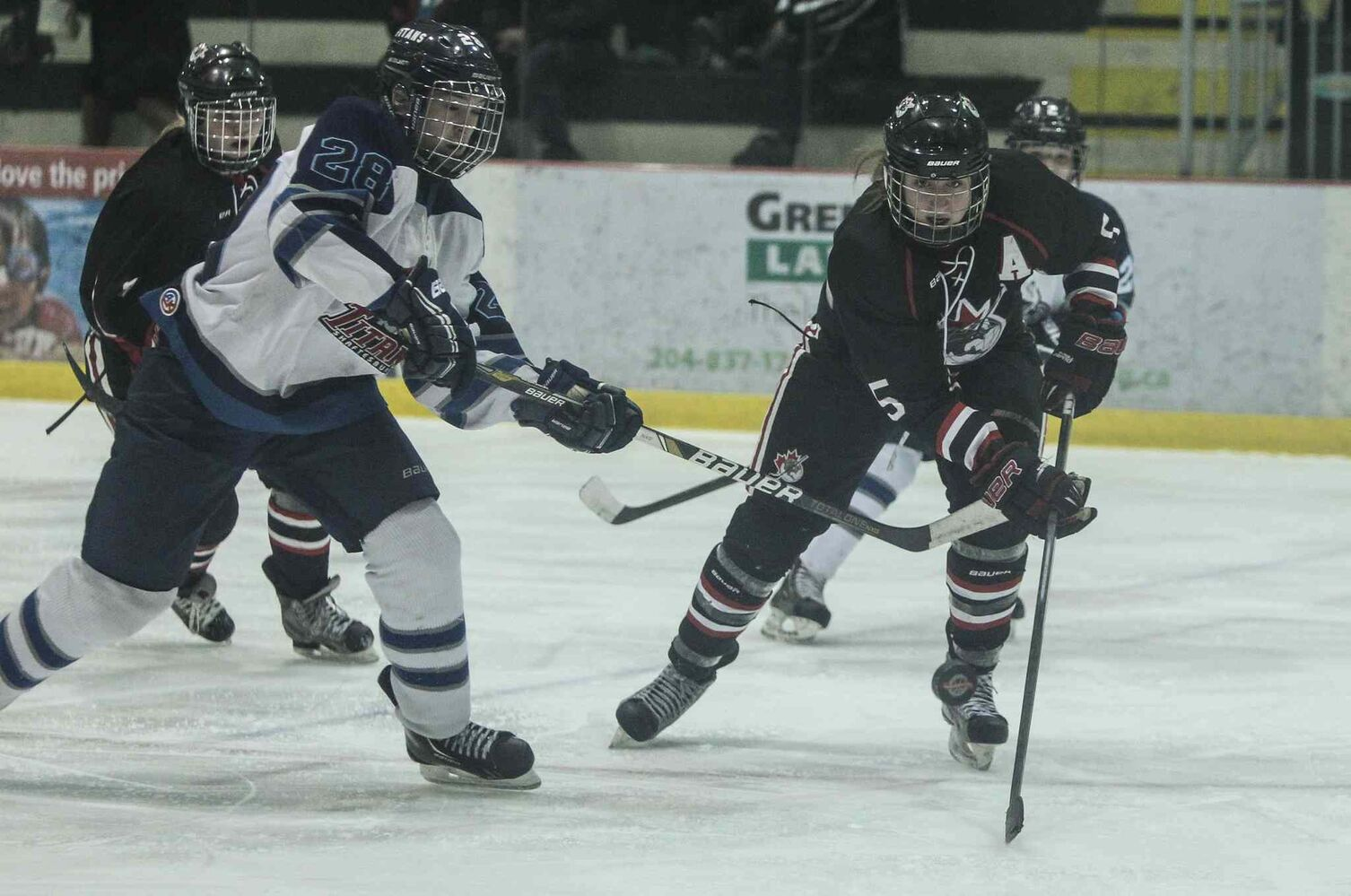 The Shaftesbury Titans' Kayla Mee (left) tries to prevent the POEs' Danielle Hardy from getting a breakaway during the second period.