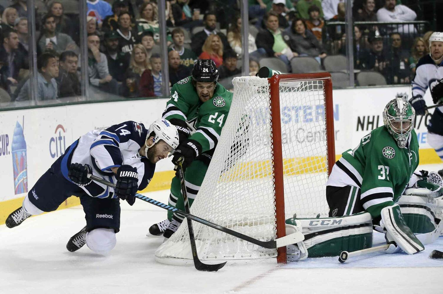 Winnipeg Jets' Anthony Peluso (left) dives to take a shot around the net against Dallas Stars goalie Kari Lehtonen (right) as Jordie Benn gives chase. (Tony Gutierrez / The Associated Press)