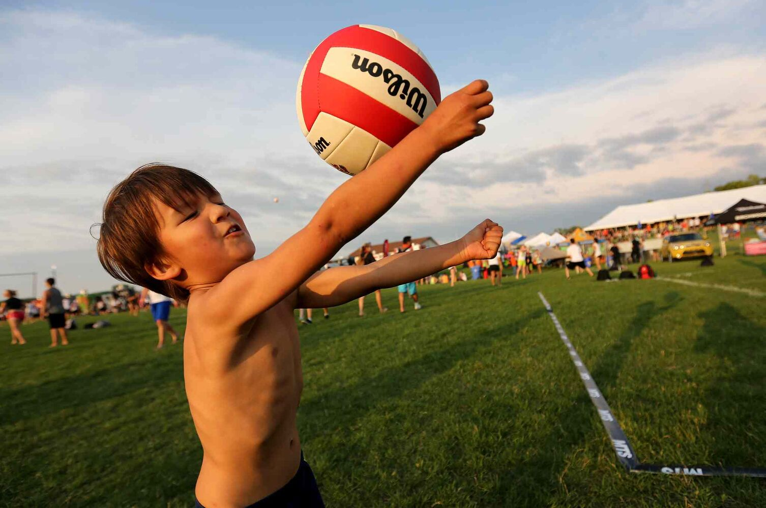 Alexander Schinkel, 3, playing with a ball at the Super-Spike volleyball tournament at Maple Grove Rugby Park, Friday, July 18, 2014.