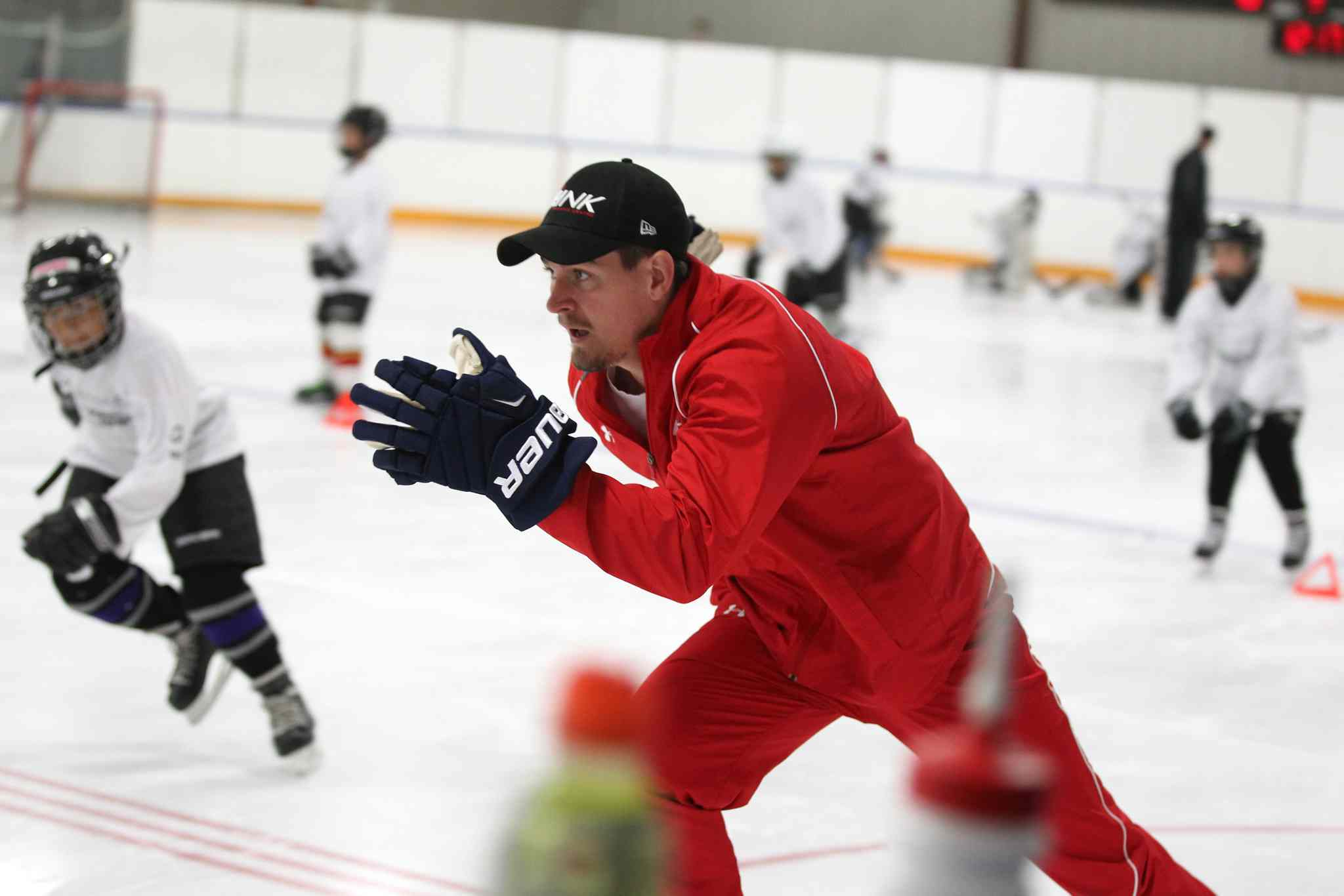 Mark Scheifele works with young hockey players on the ice.