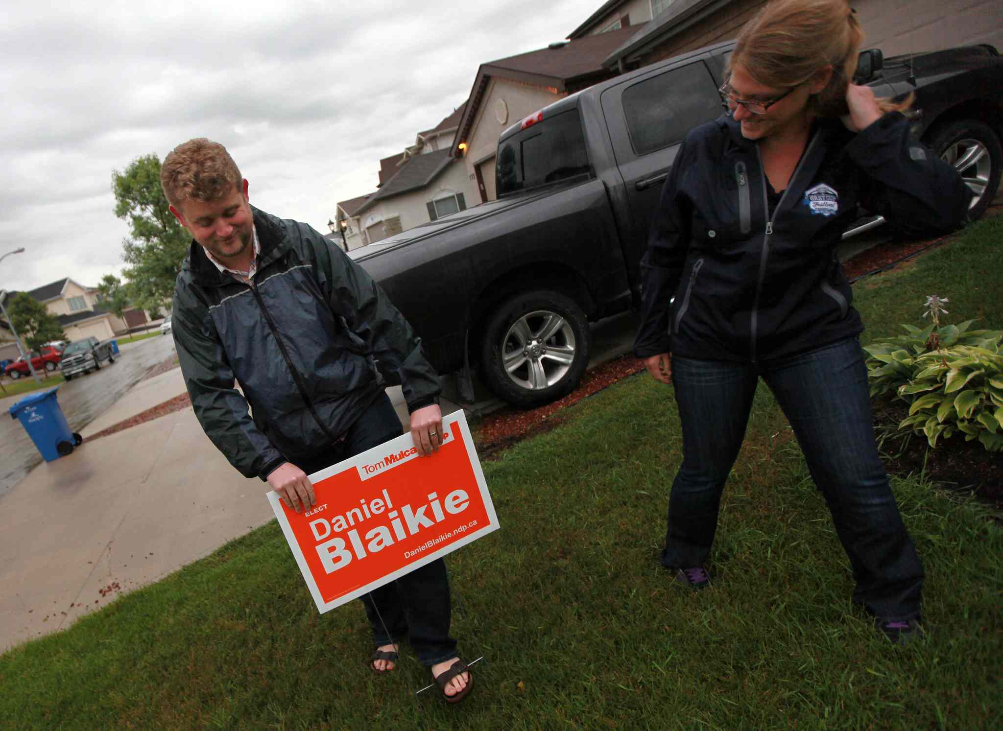 Daniel Blaikie pushes a campaign sign into a transcona lawn Wednesday evening assisted by Breigh Kusmack. The sign at 171 Chadwick Cr. was the first in the area. (Phil Hossack / Winnipeg Free Press)