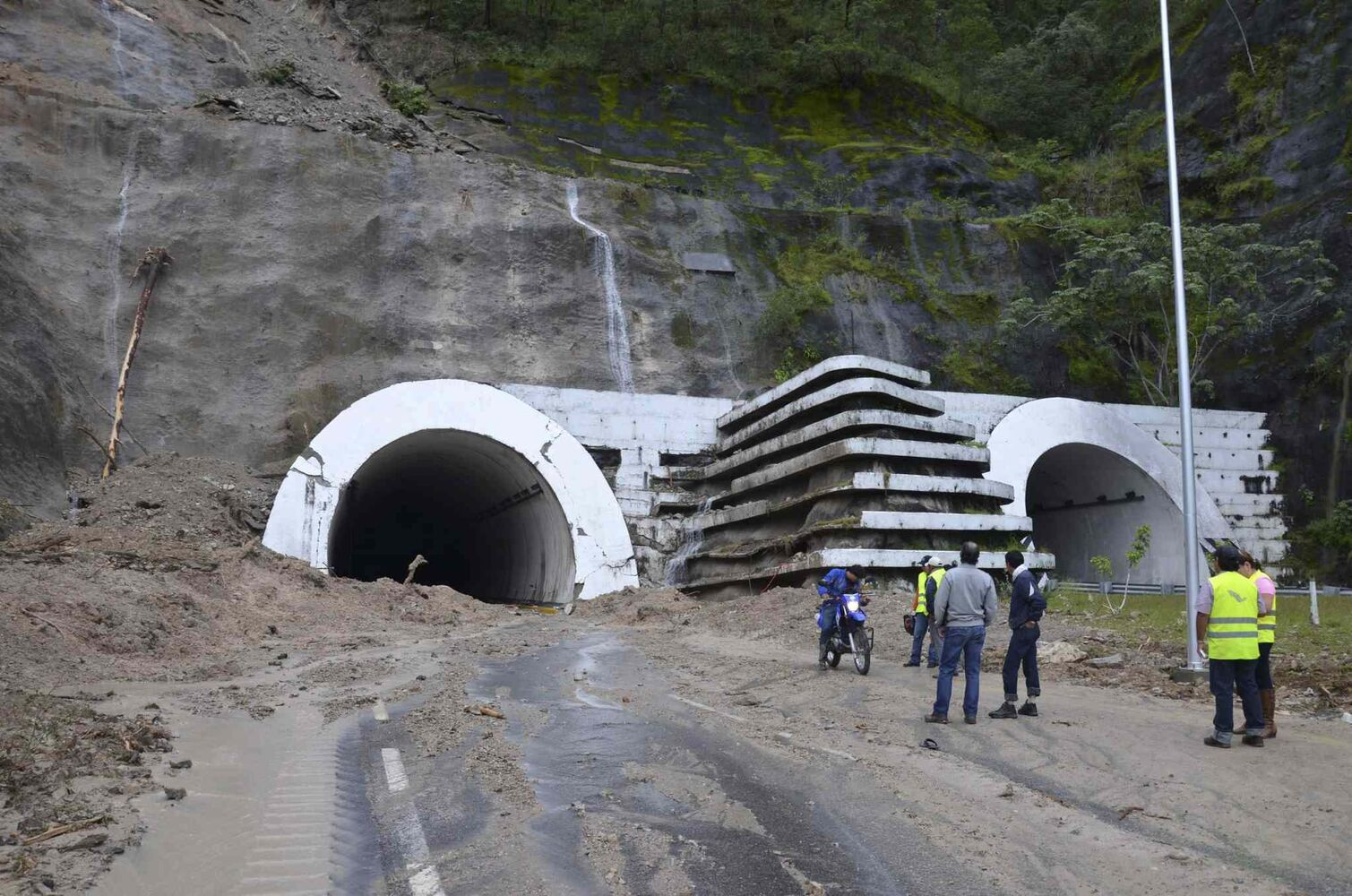 People stand at the entrance to the badly damaged Agua de Obispo tunnel that connects Acapulco and Chilpancingo, near Chilpancingo, Mexico, Tuesday, Sept. 17, 2013. As many as 60,000 tourists, many of whom traveled from Mexico City for a long holiday weekend, found themselves stranded in Acapulco, with the airport flooded and highways blocked by landslides and water caused by Tropical Storm Manuel.