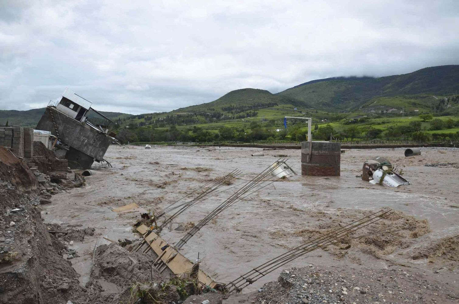 A home dangles on the banks of the Huacapa River overflowed due to heavy rains caused by Tropical Storm Manuel near the town of Petaquillas, Mexico, Tuesday, Sept. 17, 2013. An unknown number of homes were badly damaged by landslides and flooding. (Alejandrino Gonzalez / The Associated Press)