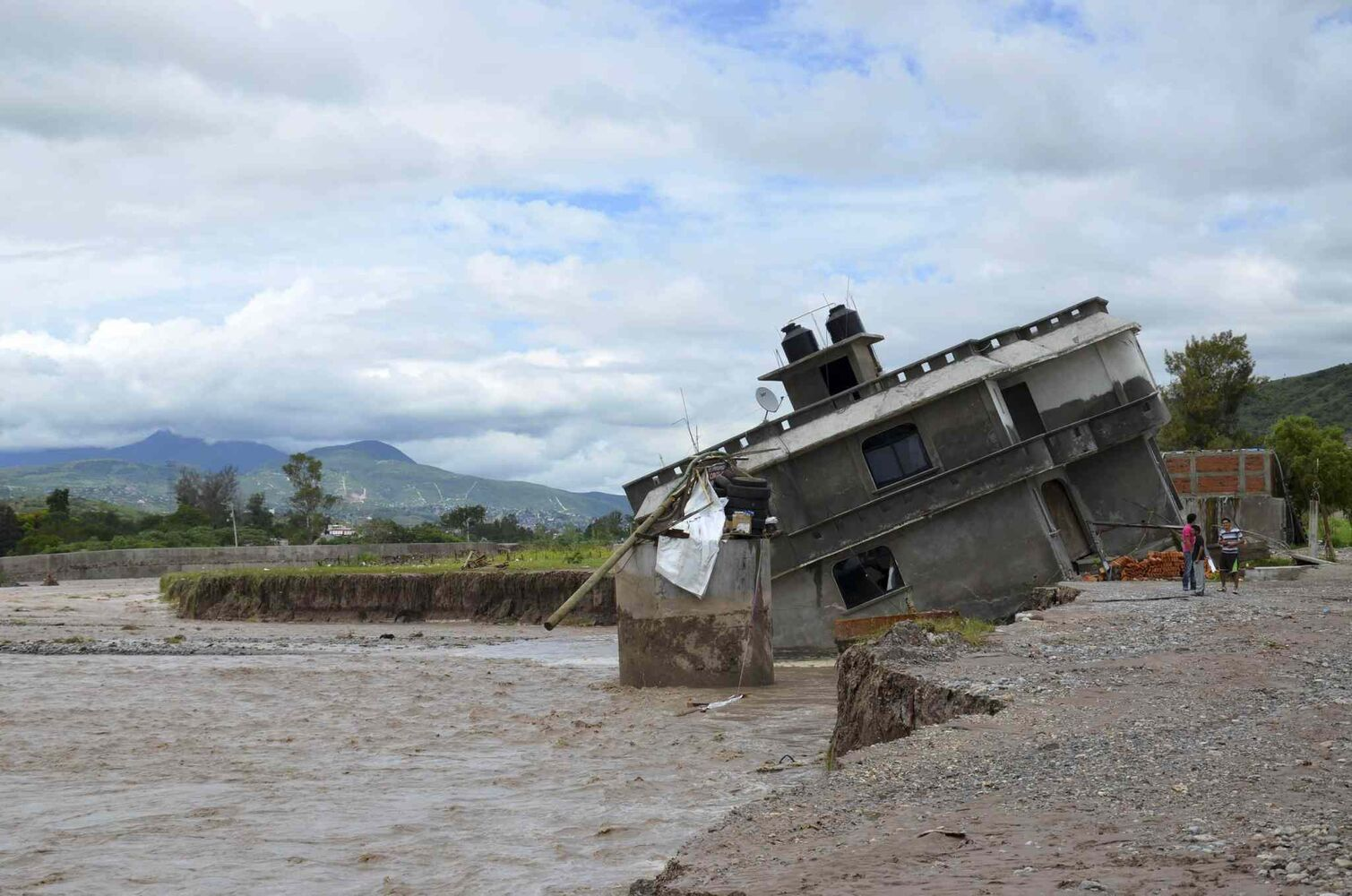 People stand next to home collapsed into the Huacapa River overflowed due to heavy rains caused by Tropical Storm Manuel near the town of Petaquillas, Mexico, Tuesday, Sept. 17, 2013.