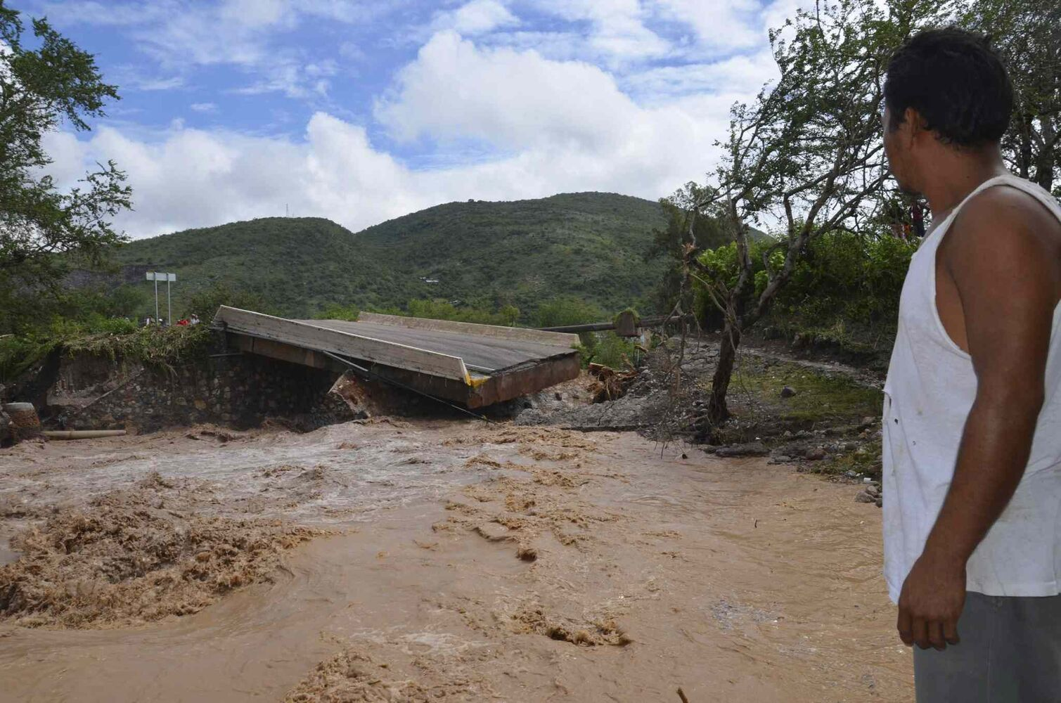 A man watches a collapsed bridge over the Huacapa River near the town of Petaquillas, Mexico, Tuesday, Sept. 17, 2013.