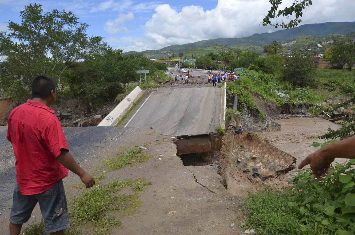 A man looks at a collapsed bridge over the Huacapa River near the town of Petaquillas, Mexico, Tuesday, Sept. 17, 2013.