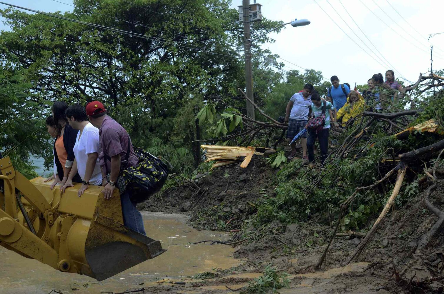 People are aided with the help of a bulldozer to cross a road after a landslide caused by heavy rains brought by Tropical Storm Manuel on the outskirts of Acapulco, Mexico, Monday Sept. 16, 2013.  (Bernandino Hernandez / The Associated Press)