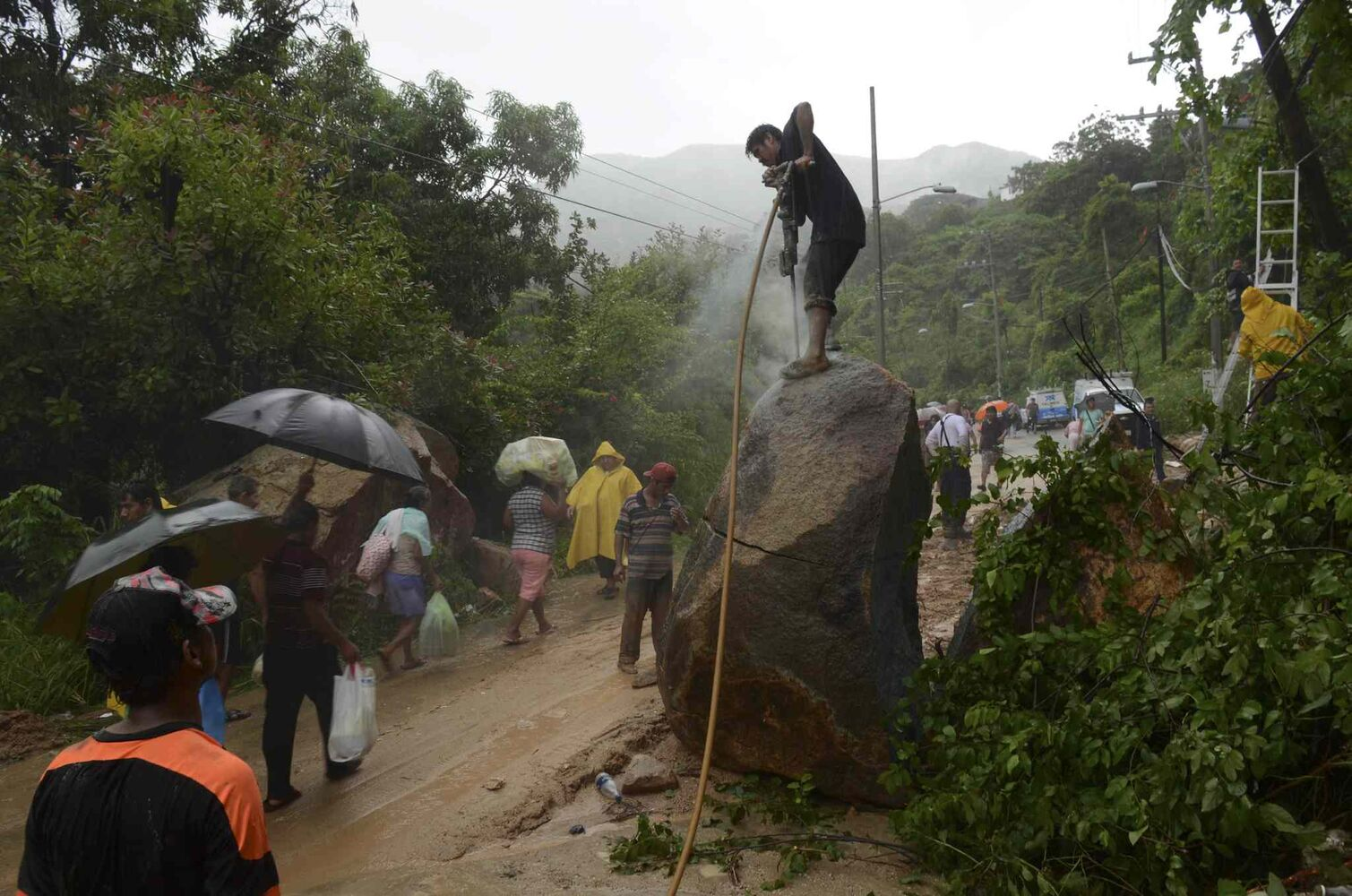 A man works to break apart a boulder with a jackhammer as people make their way on foot, near a road that was cut off after heavy rains brought on by Tropical Storm Manuel triggered a landslide, on the outskirts of Acapulco, Mexico, Monday, Sept. 16, 2013.