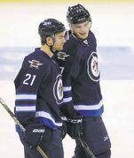 Jets T.J. Galiardi (21) and Adam Lowry chat after Lowry's goal.