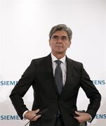 Joe Kaeser, CEO of German industrial conglomerate Siemens, arrives for a news conference prior to the annual shareholder meeting in Munich, Germany, Tuesday, Jan. 27, 2015. Industrial machinery maker Siemens AG said net profit fell 25 percent in its most recent quarter as revalued financial derivatives and lower earnings at its key power and gas business weighed on the bottom line. (AP Photo/Matthias Schrader)
