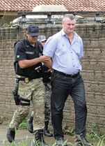 In this Feb. 22, 2015 photo released by Jornal Folha Do Progresso, Ezequiel Antonio Castanha is escorted in handscuffs by a federal police officer in Novo Progresso, Brazil. The Brazilian Institute of Environment and Renewable Natural Resources said Castanha, who was detained Saturday in the state of Para, operated a network that illegally seized federal lands, clear-cut them and sold them to cattle grazers. (AP Photo/Jornal Folha do Progresso, Juliano Simionato)