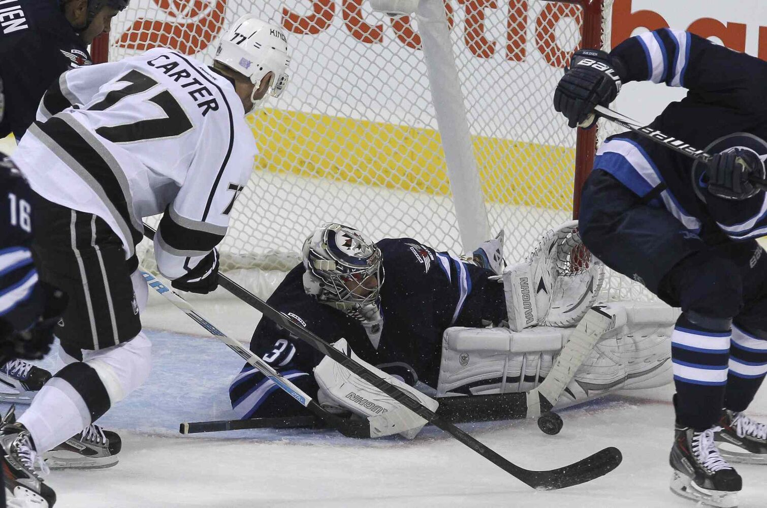 Winnipeg Jets' goaltender Ondrej Pavelec (31) makes a save while Los Angeles Kings' Jeff Carter (77) goes for a rebound in the third period.