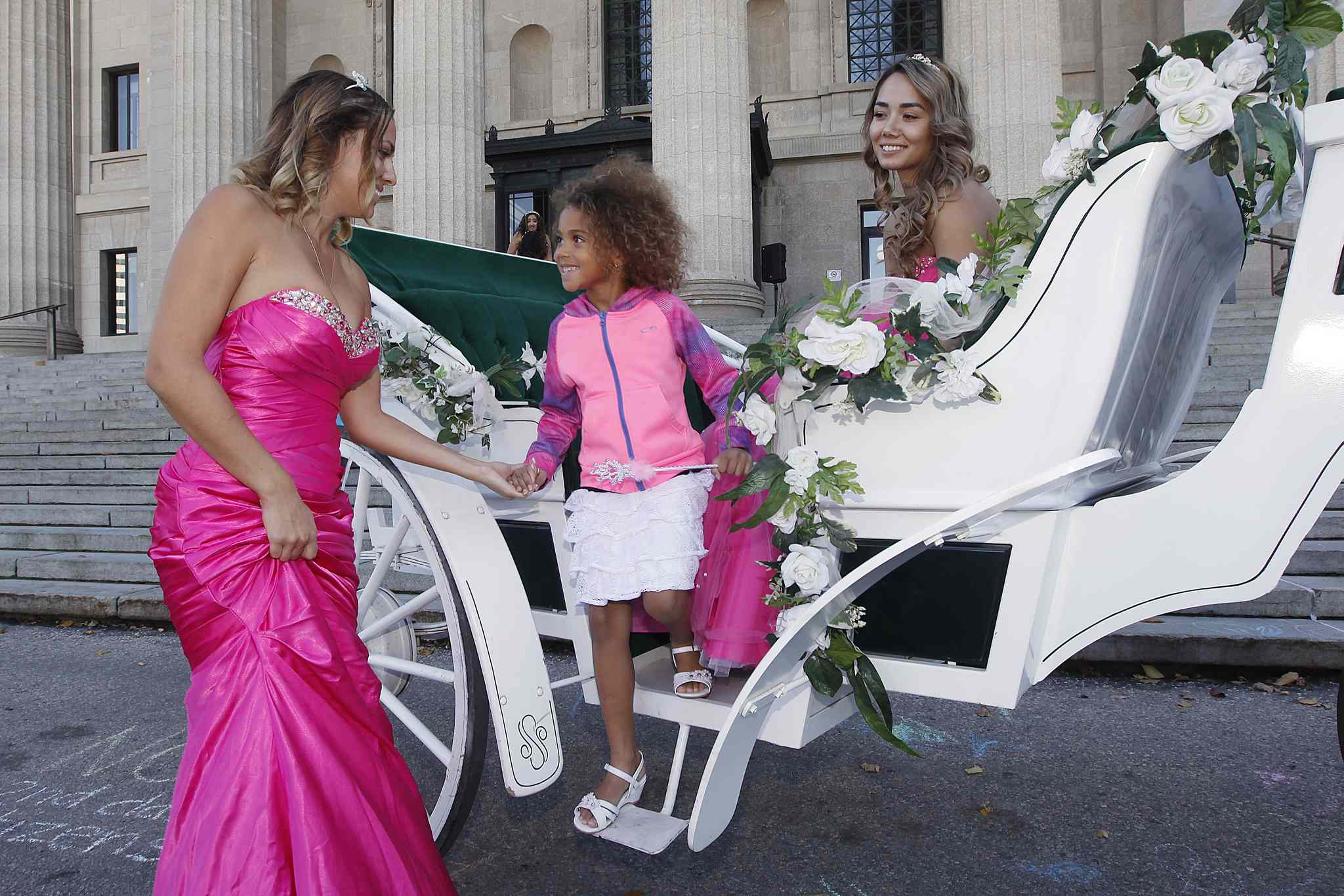 Arriving in style: Princess Gillian Bridges helps Princess Kyanna Speiss off a horse-drawn carriage as Princess Tiffany Tran watches at the Princess For a Day fundraiser Sunday at the Manitoba Legislative Building.