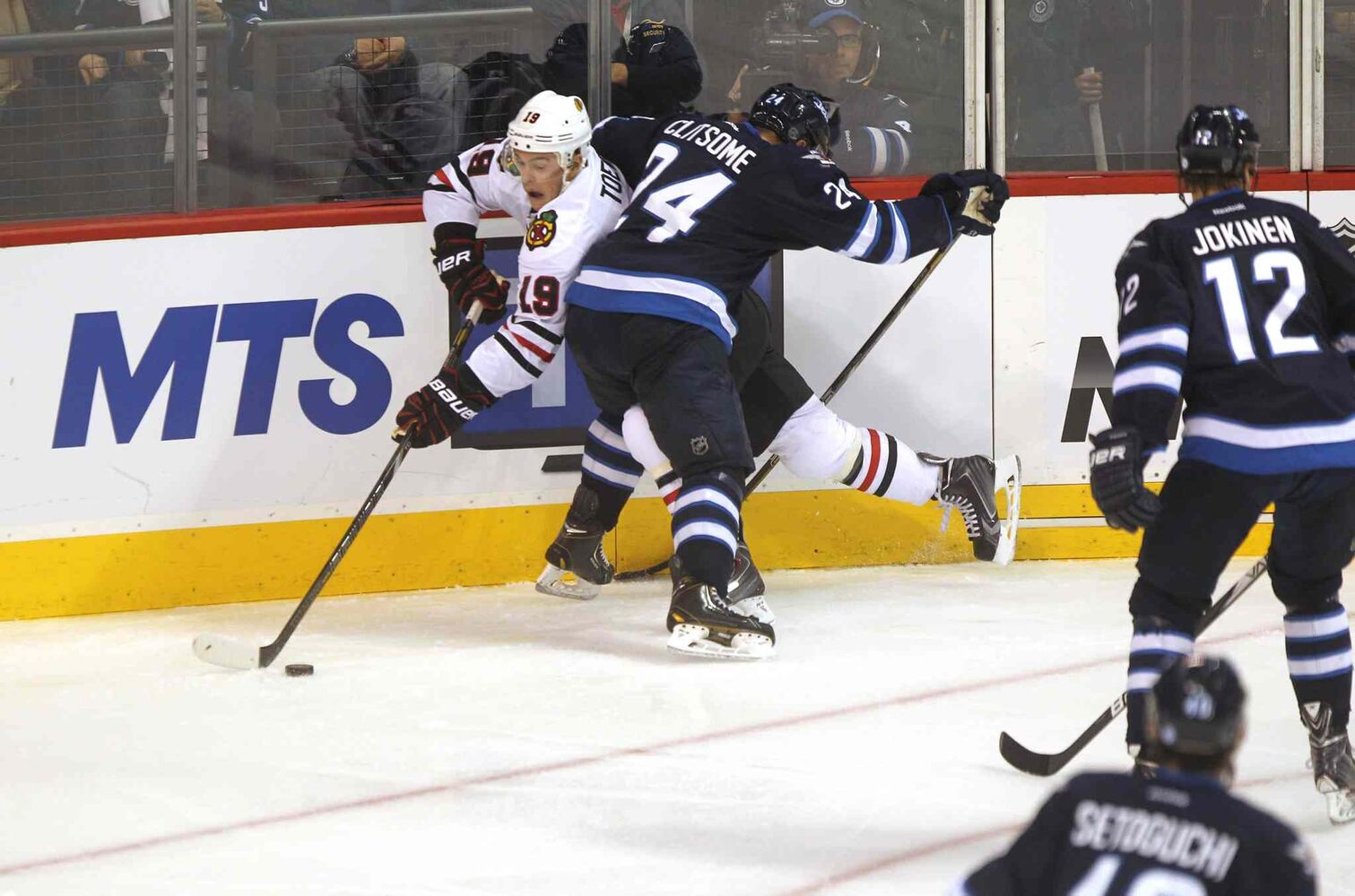 Grant Clitsome (24) checks Jonathan Toews (left) as Olli Jokinen (12) looks on during the third  period. (Ruth Bonneville / Winnipeg Free Press)