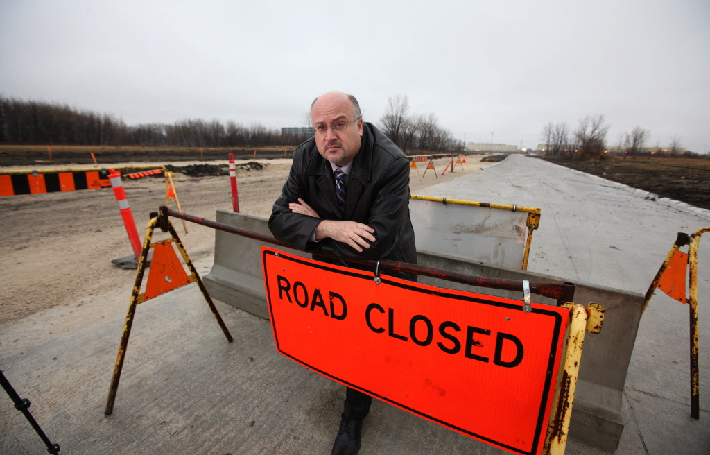 """Transcona Coun. Russ Wyatt leans on the """"road closed"""" sign blocking access to the east end of Reenders road Tuesday.  Ruth Bonneville / Winnipeg Free Press"""