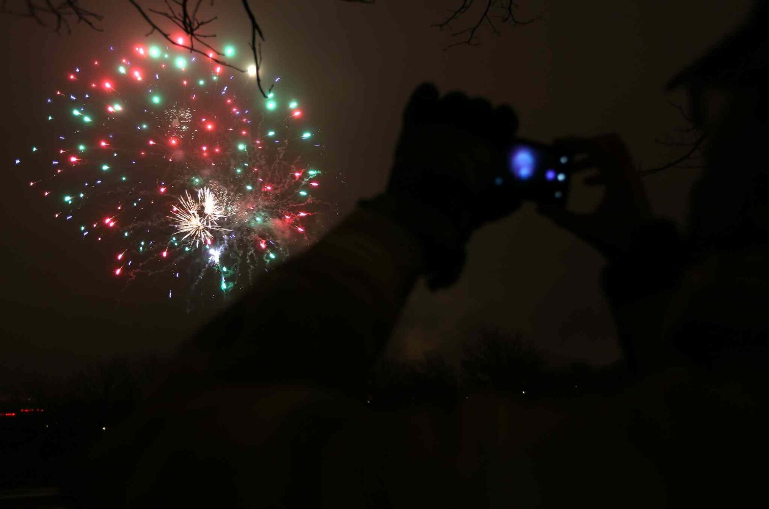 A spectator takes a photo of fireworks set off at The Forks following the parade.