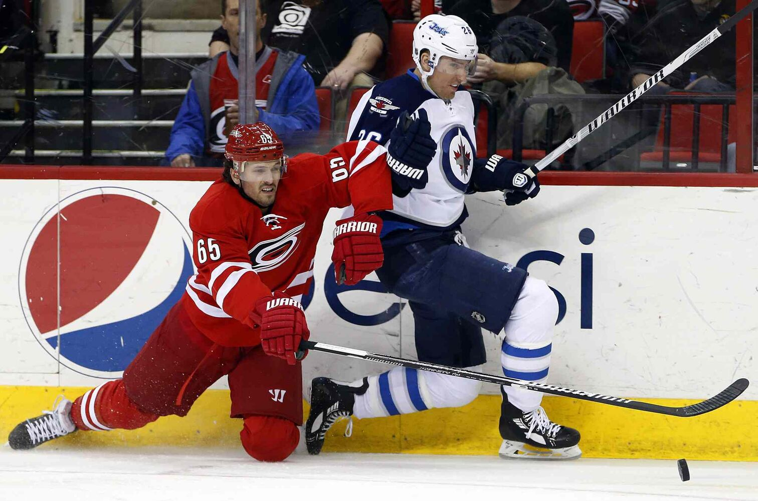 Winnipeg Jets' Blake Wheeler (26) and Carolina Hurricanes' Ron Hainsey (65) collide along the boards during the first period of Tuesday's game.