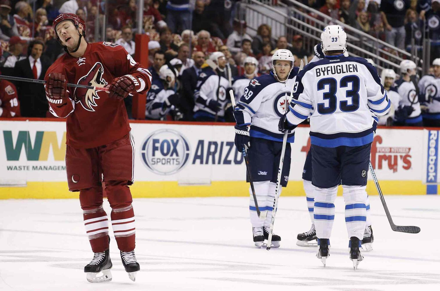 Winnipeg Jets' Dustin Byfuglien (33) and Toby Enstrom (39), of Sweden, celebrate a goal by teammate Blake Wheeler as Arizona Coyotes' David Moss, left, skates dejectedly away during the first period of an NHL hockey game Thursday. (Ross D. Franklin / The Associated Press)