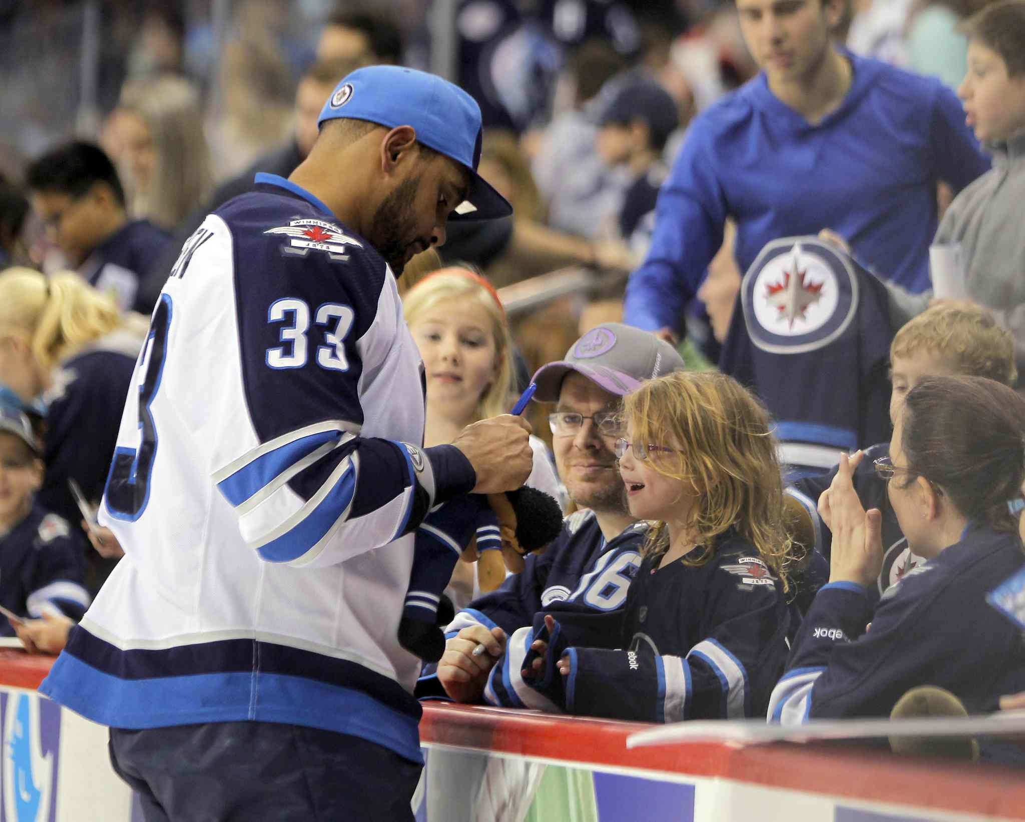 Dustin Byfuglien sign autographs during the Winnipeg Jets Skills competition last week.