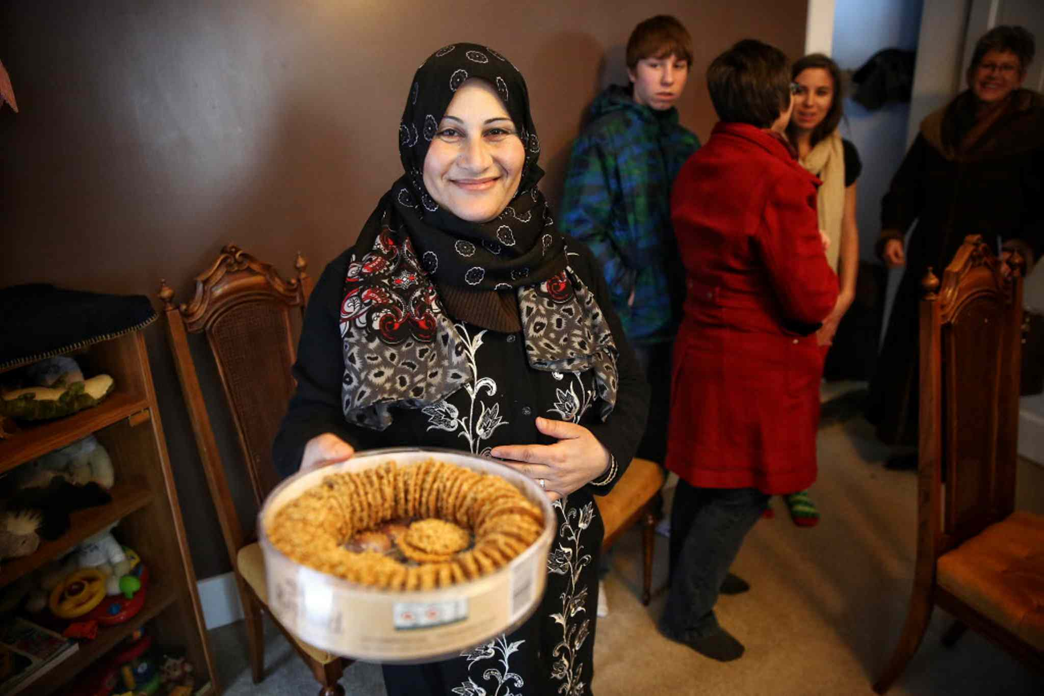 A very happy Ahlam Dib serves cookies and coffee to the crowd of volunteers that arrived at her new home in Altona to welcome her and her husband and their seven children.