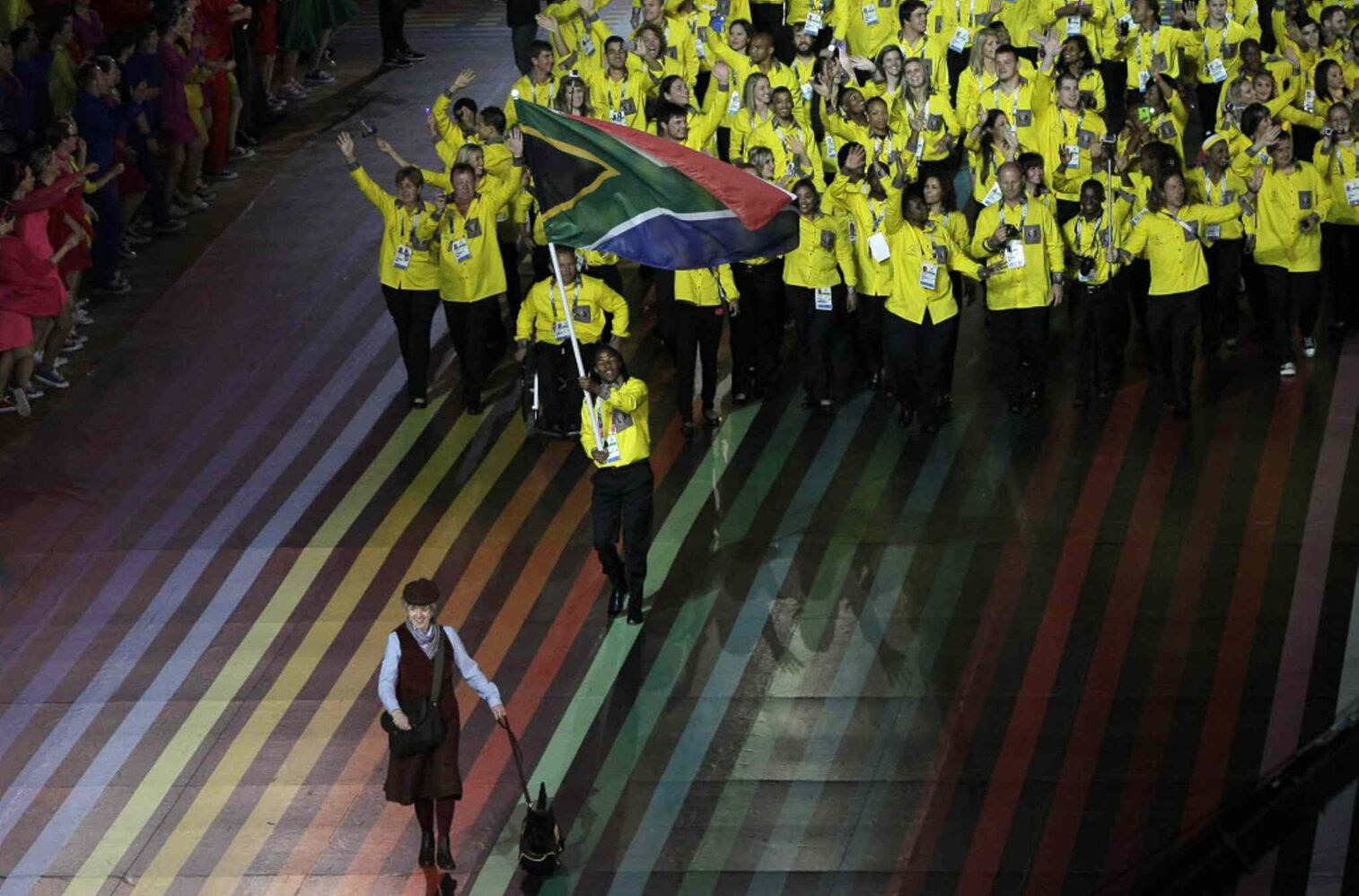 South Africa's flag bearer Cecil Sebastian Afrika leads the team during the opening ceremony for the Commonwealth Games 2014 in Glasgow, Scotland, Wednesday. (Kirsty Wigglesworth / The Associated Press)