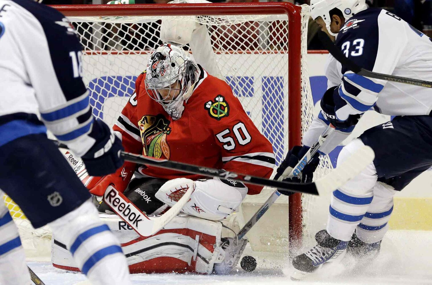 Chicago Blackhawks goalie Corey Crawford (50) saves a shot by Winnipeg Jets defenceman Dustin Byfuglien (33) during the first period.