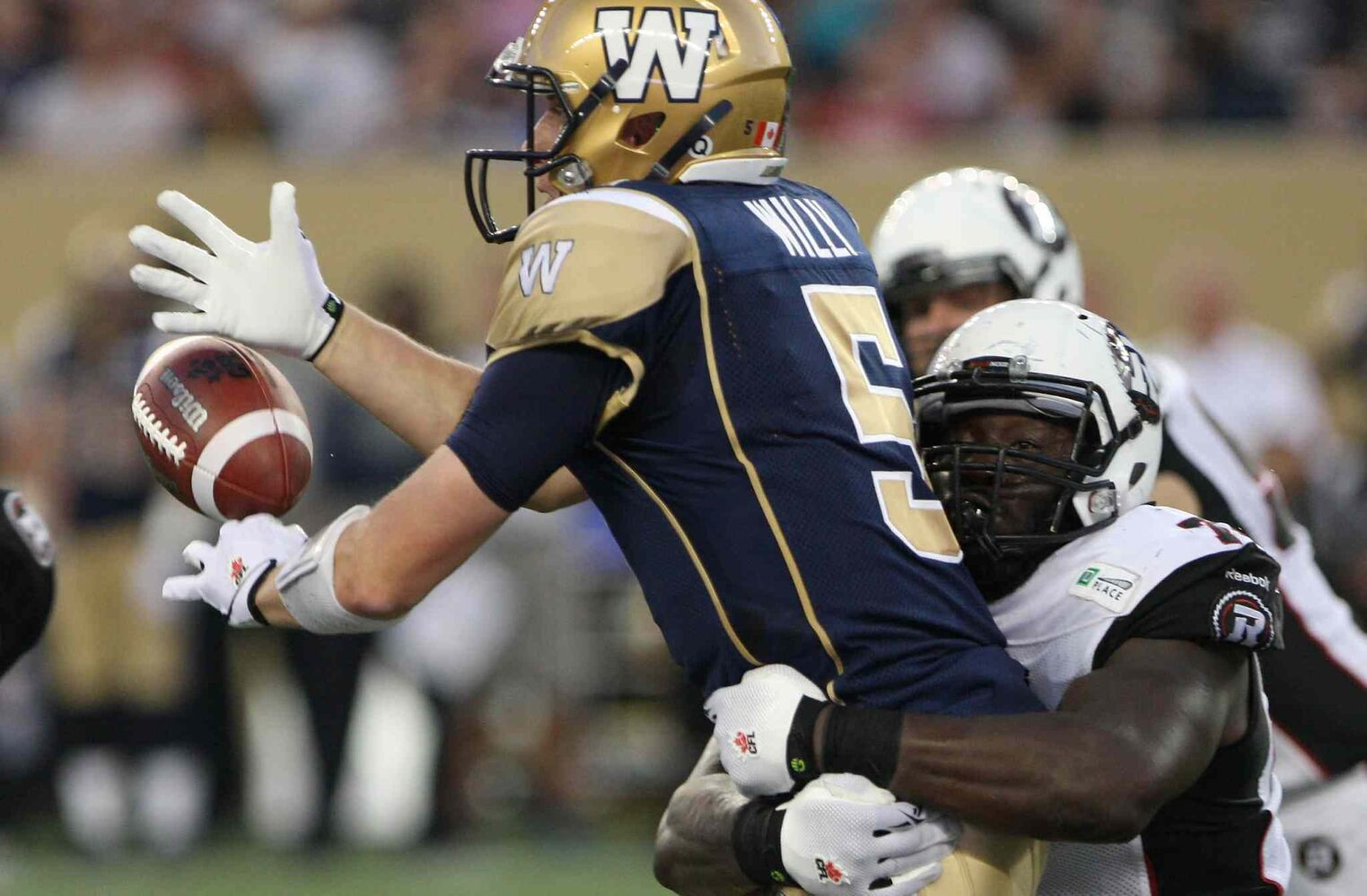 Winnipeg Blue Bombers' quarterback Drew Willy takes a big hit from Ottawa Redblacks' Jonathan Williams during the second half of Thursday's game. (JOE BRYKSA / WINNIPEG FREE PRESS)