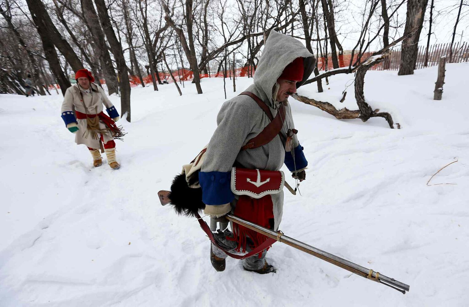 Actors in a historical reenactment between la Compagnie de La Verendrye and The Forces of Lord Selkirk trudge through the snow at The Festival du Voyageur Sunday.