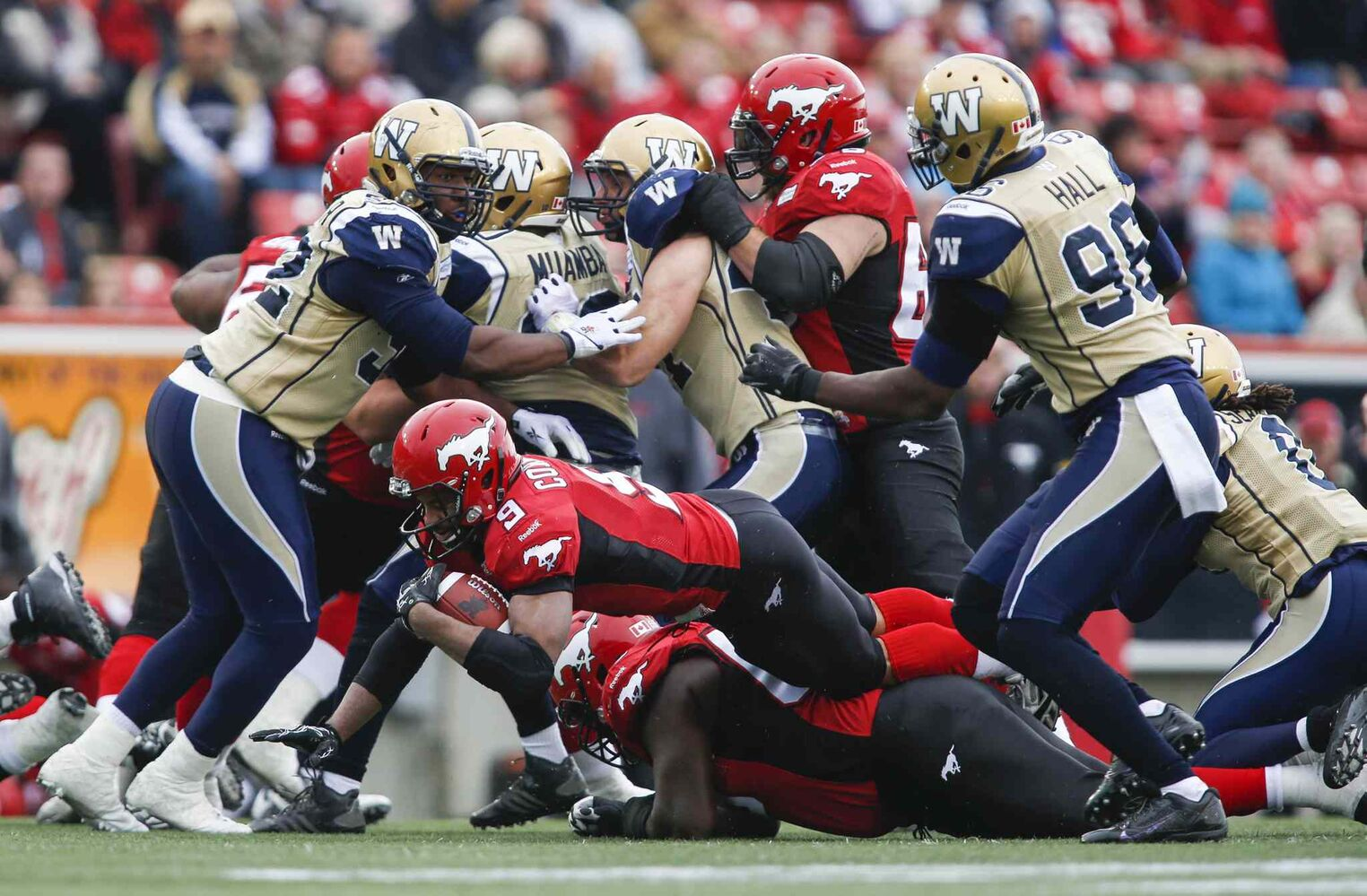 Winnipeg Blue Bombers' Bryant Turner Jr. (left) and Alex Hall (right) look on as Calgary Stampeders' Jon Cornish (centre) dives for more yards during the first half. (Jeff McIntosh / The Canadian Press)