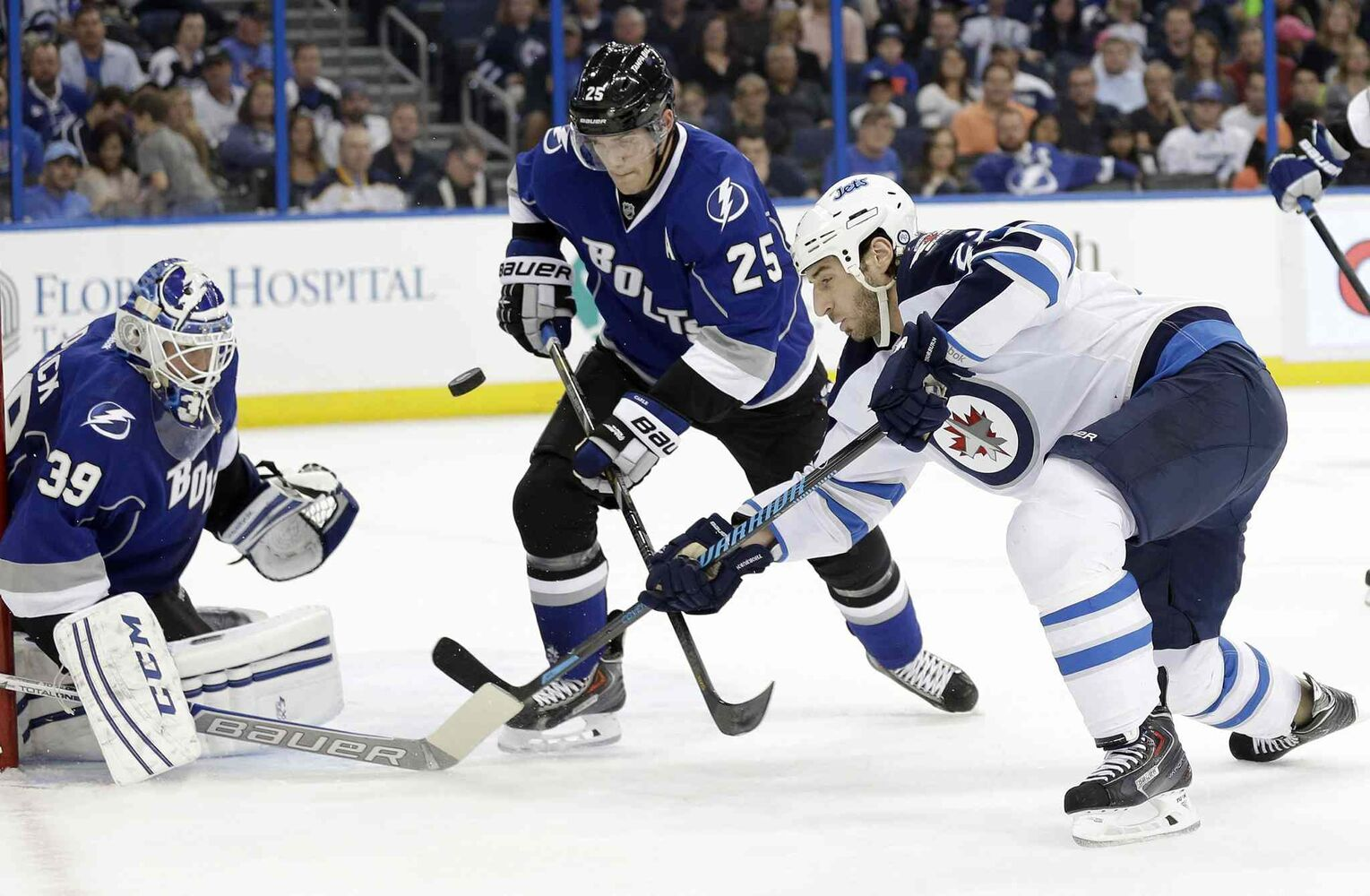 Winnipeg Jets winger Chris Thorburn (right) shoots on Tampa Bay Lightning goalie Anders Lindback (left) as Lightning defenceman Matt Carle moves in during the first period. (Chris O'Meara / The Associated Press)