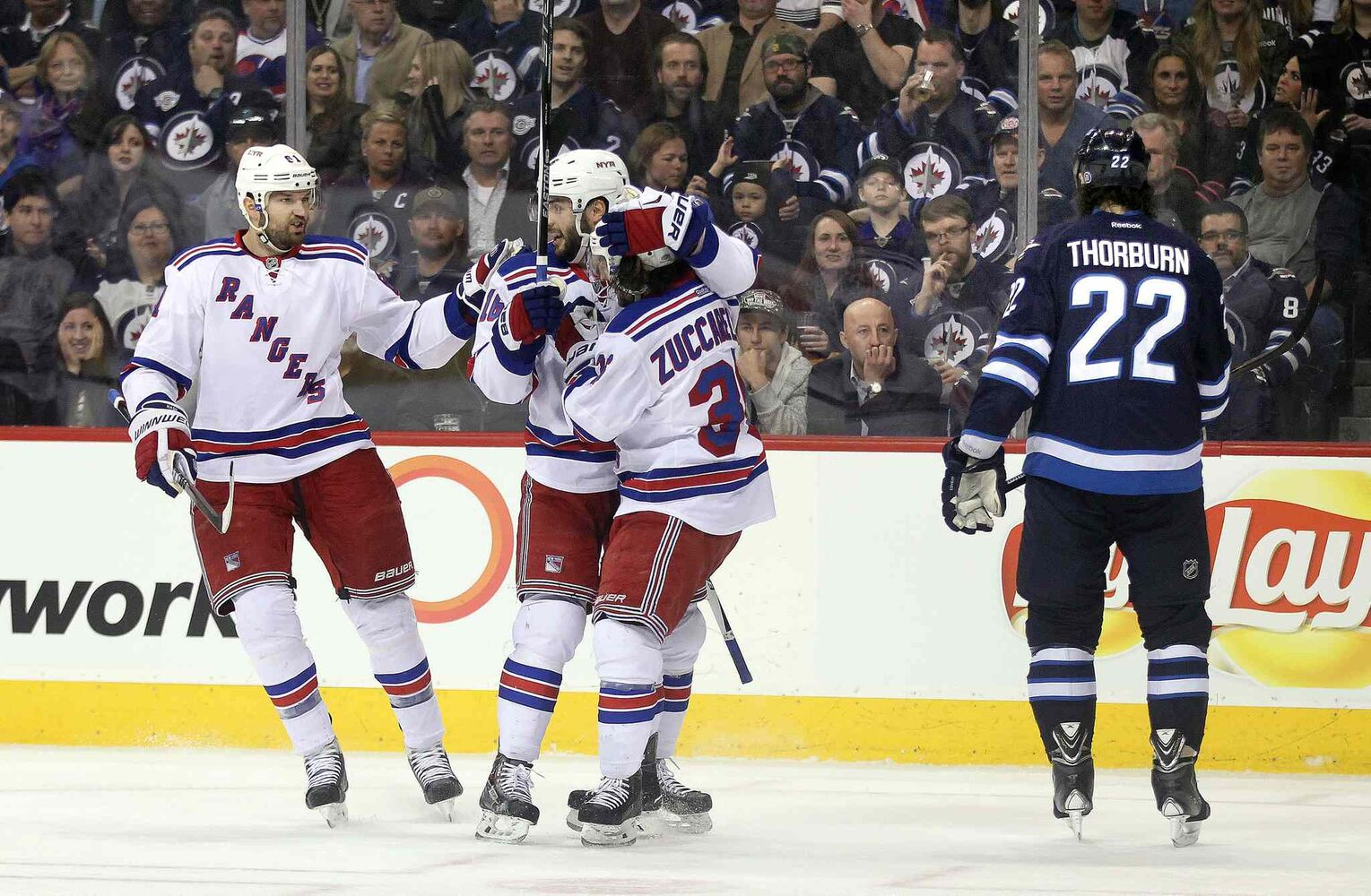 New York Rangers Rick Nash (from left) Derick Brassard and goal scorer Mats Zuccarello celebrate their answering goal against the Winnipeg Jets in the first period of Tuesday's game as Chris Thorburn skates away.   (Phil Hossack / Winnipeg Free Press)