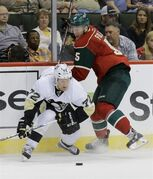 Pittsburgh Penguins right wing Patric Hornqvist (72), of Sweden, takes a hit from Minnesota Wild defenseman Christian Folin (5) as they chase the puck during the second period of a preseason NHL hockey game in St. Paul, Minn., Monday, Sept. 29, 2014. (AP Photo/Ann Heisenfelt)