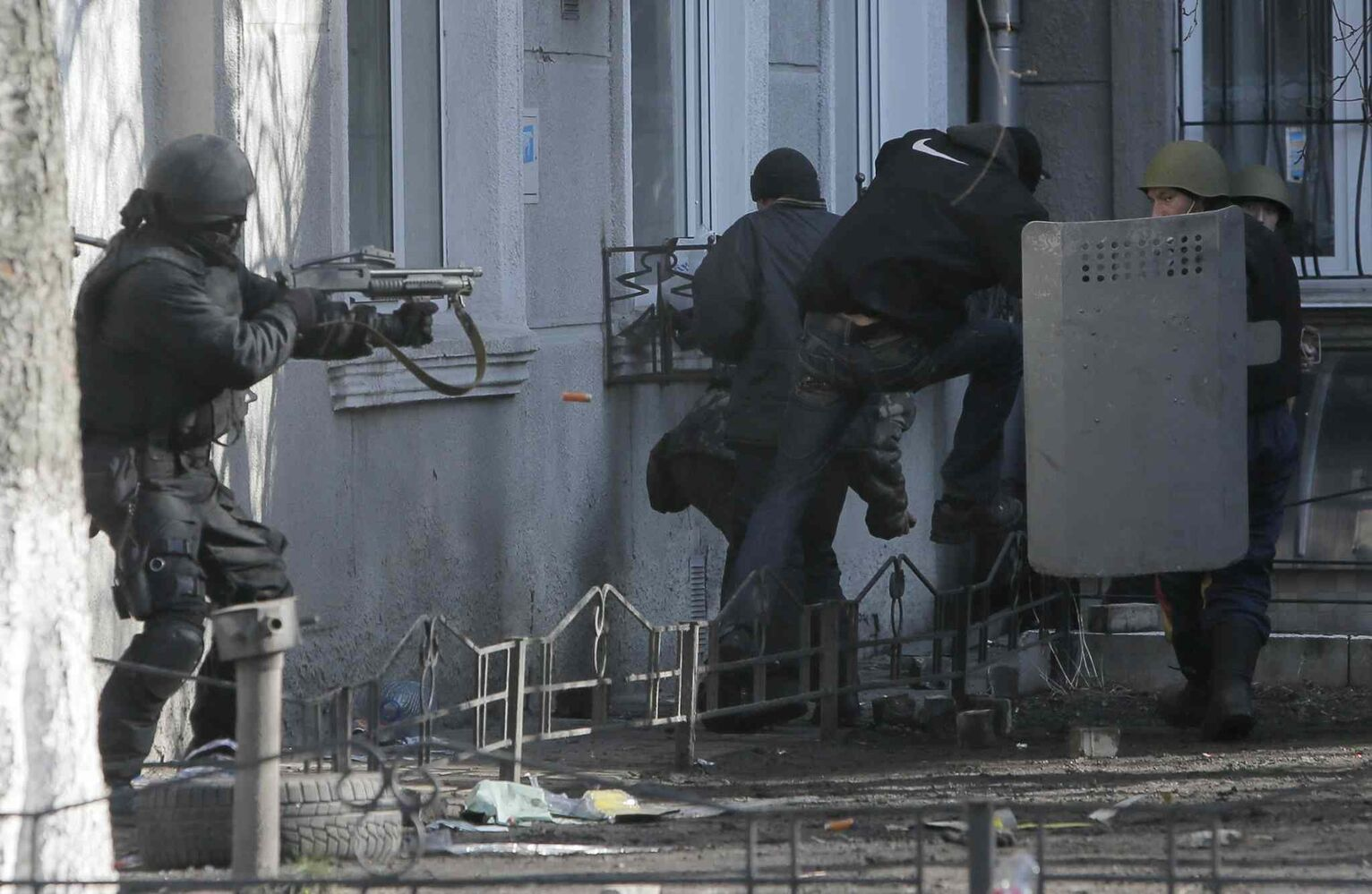 A riot police officer shoots at protesters outside Ukraine's parliament in Kyiv on Tuesday. (Efrem Lukatsky / The Associated Press)