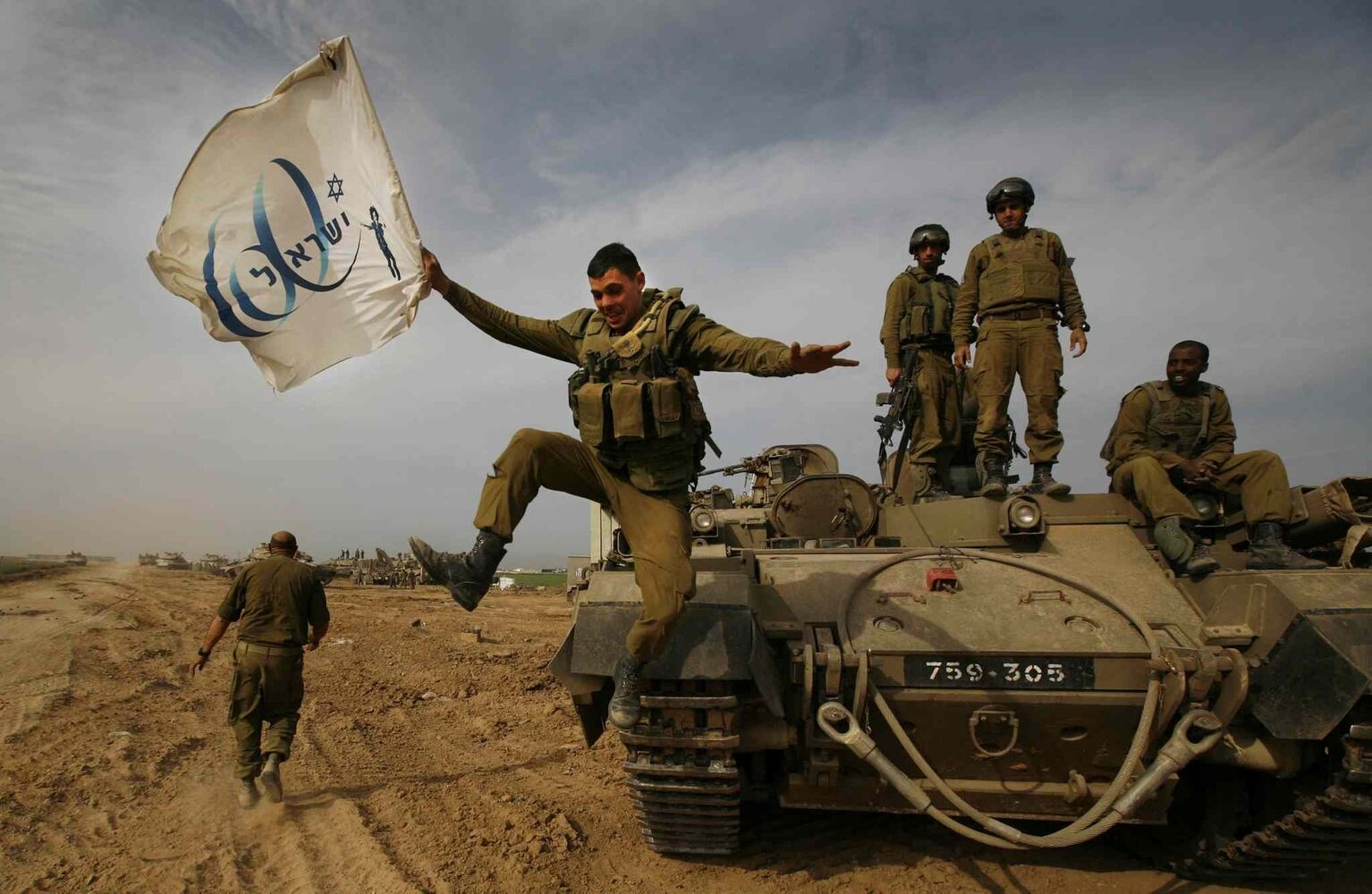 Friday, Jan. 16, 2009: An Israeli soldier jumps off an armored vehicle carrying a flag of Israel's 60th anniversary as he celebrates with his unit their return from the Gaza Strip on the Israeli side of the border.  (Anja Niedringhaus / The Associated Press)