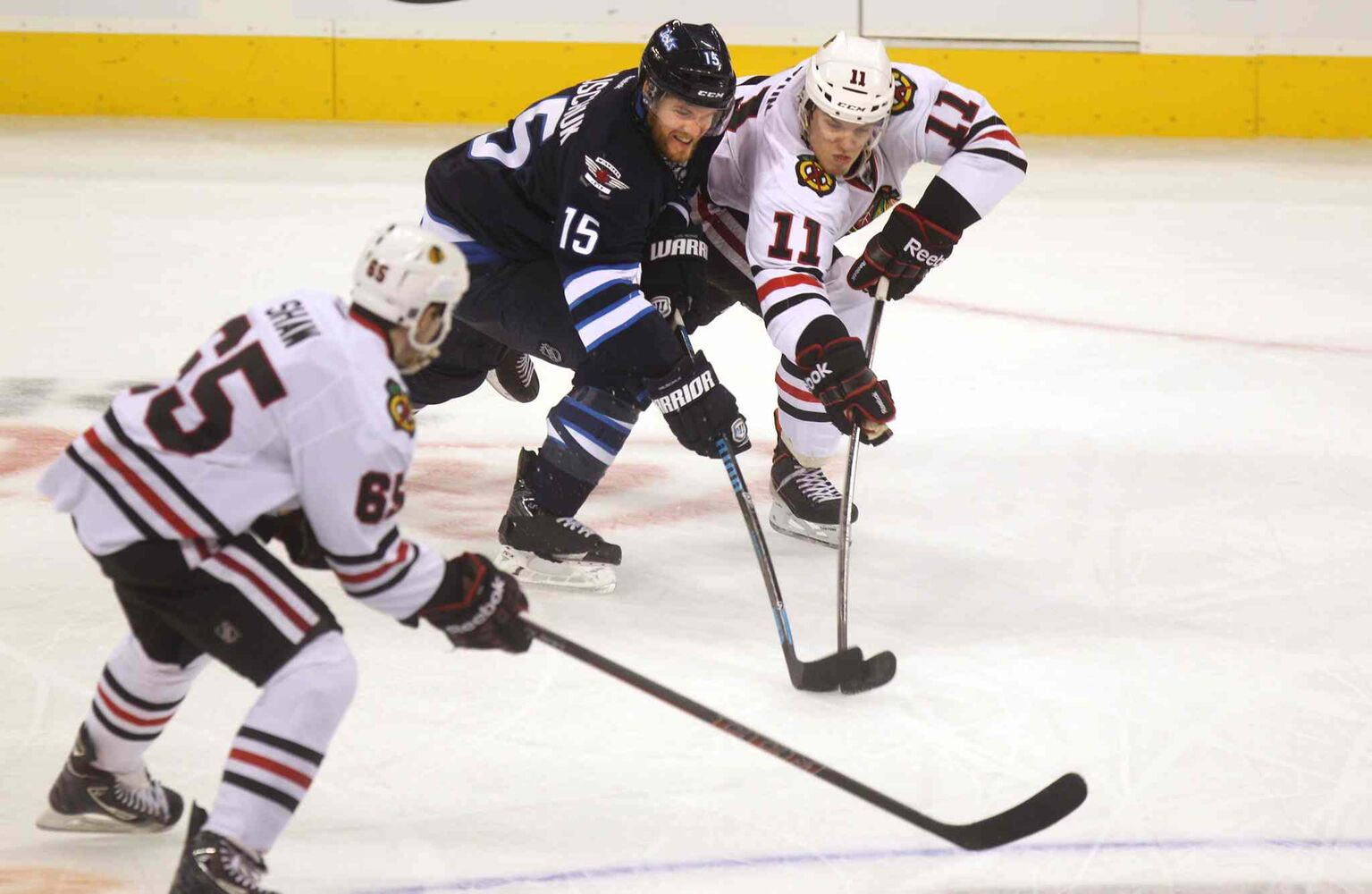 Matt Halischuk (centre) tries to get the puck from Jeremy Morin (right) during the third period. (Ruth Bonneville / Winnipeg Free Press)