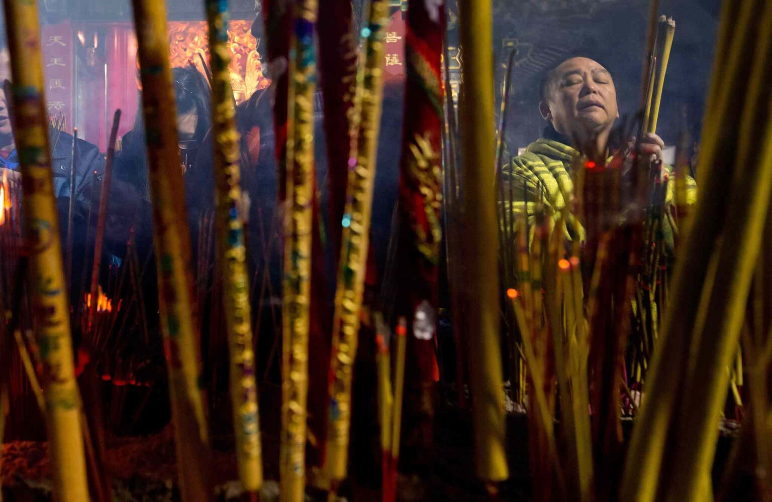 A man is framed by burning incense sticks as he prays to mark the Lunar New Year at the International Buddhist Temple in Richmond, B.C., during the early morning hours of Friday, January 31, 2014.  (Darryl Dyck / The Canadian Press)