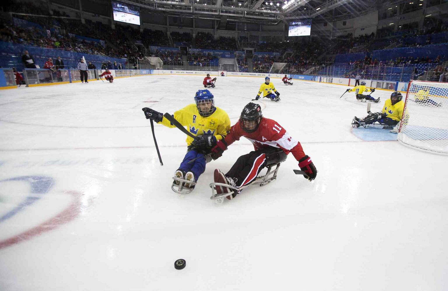 Marcus Holm of Sweden, center left, and Adam Dixon of Canada, center right, chase the puck during the ice sledge hockey match at the Shayba Arena at the 2014 Winter Paralympics in Sochi, Russia, Saturday, March 8, 2014.   (Pavel Golovkin / The Associated Press)