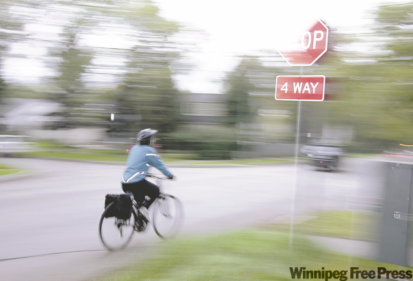 TREVOR HAGAN / WINNIPEG FREE PRESS A cyclist rolls through a stop sign at the intersection of Grosvenor Avenue and Waverley Street on Monday.
