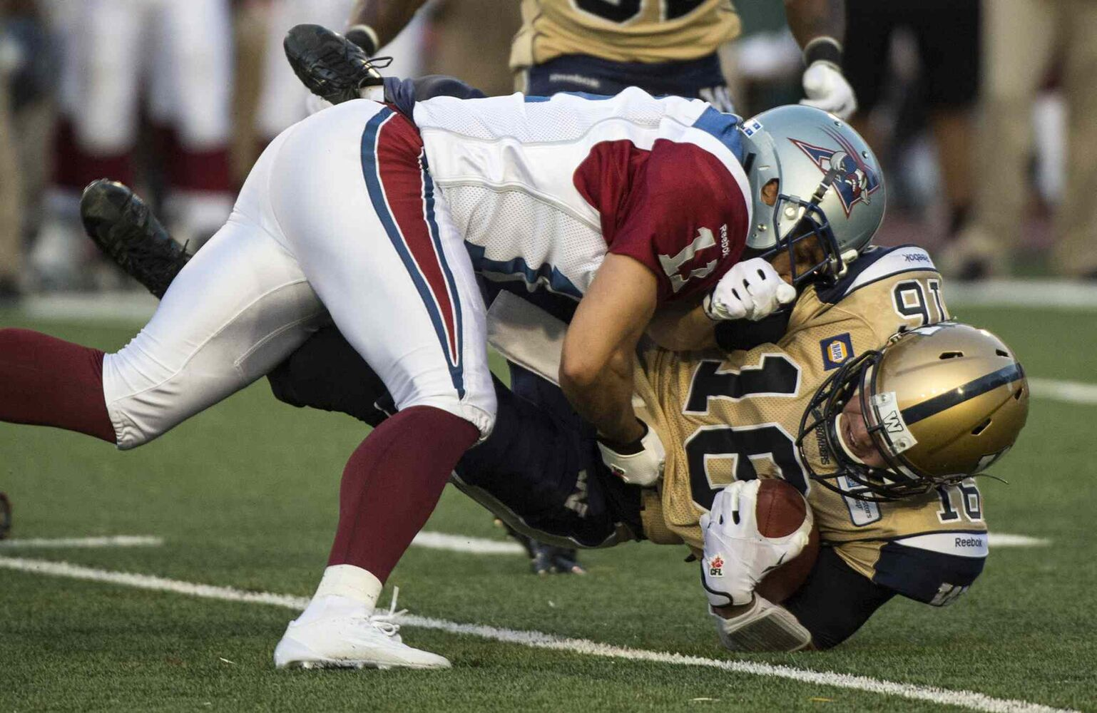 Winnipeg Blue Bombers' quarterback Robert Marve is tackled by Montreal Alouettes' linebacker Chip Cox in the second quarter of Friday's game. (Paul Chiasson / The Canadian Press)
