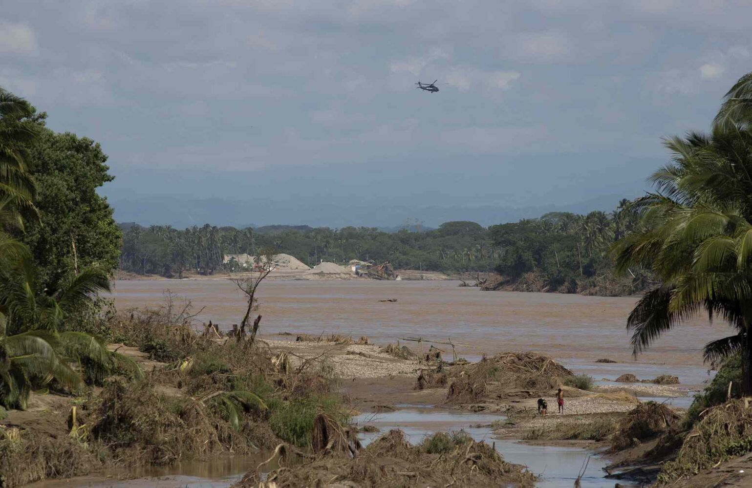 A federal police helicopter flies over a river, south of Acapulco, near the town of Lomas de Chapultepec, Guerrero state, Mexico, Wednesday, Sept. 18, 2013.  Emergency flights began arriving in Acapulco to evacuate at least 40,000 mainly Mexican tourists stranded in the resort city.  (Eduardo Verdugo / The Associated Press)