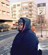 In a photo from Feb. 12, 2015, Alison Norris, 26, waits for a public bus in Detroit. Norris catches at least two buses during a 2-hour, one-way commute from Detroit to her restaurant hostess job in the city's northern suburbs. She is among many Detroit residents without cars who often must travel long distances for low-paying positions in customer service or sales far outside the central city. Norris says there are too few jobs in the city. The city's unemployment rate has been estimated at more than 18 percent. (AP Photo/Corey Williams)