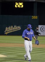 ADVANCE FOR WEEKEND EDITIONS, APRIL 25-26 - FILE - In this April 6, 2015, file photo, Texas Rangers starting pitcher Yovani Gallardo walks off the mound after throwing in the first inning as a new clock counts down in left field during their opening day baseball game against the Oakland Athletics in Oakland, Calif. The networks televising Major League Baseball games always had to weigh whether they could squeeze in one more replay or anecdote before the next pitch. Starting this season, they must factor in the sport's renewed efforts to speed up play. (AP Photo/Eric Risberg, File)