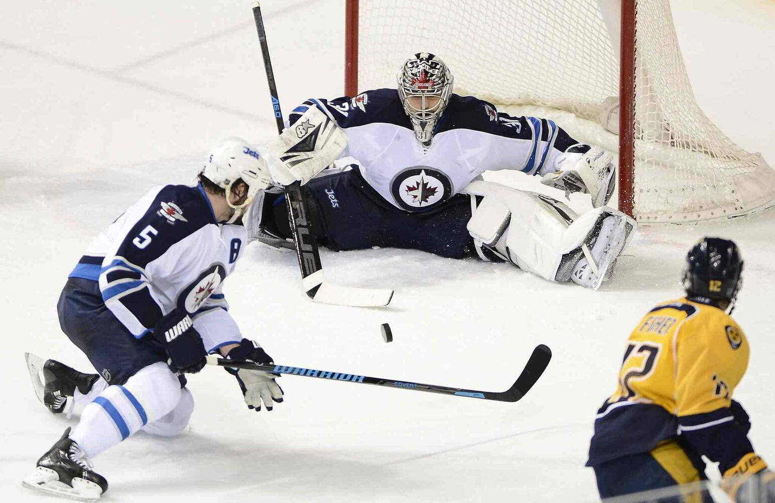 Winnipeg Jets' goalie Ondrej Pavelec (31) blocks a third-period shot from Nashville Predators' forward Mike Fisher (12) as Jets' defenseman Mark Stuart (5) tries to clear the puck. (Mark Zaleski / The Associated Press)