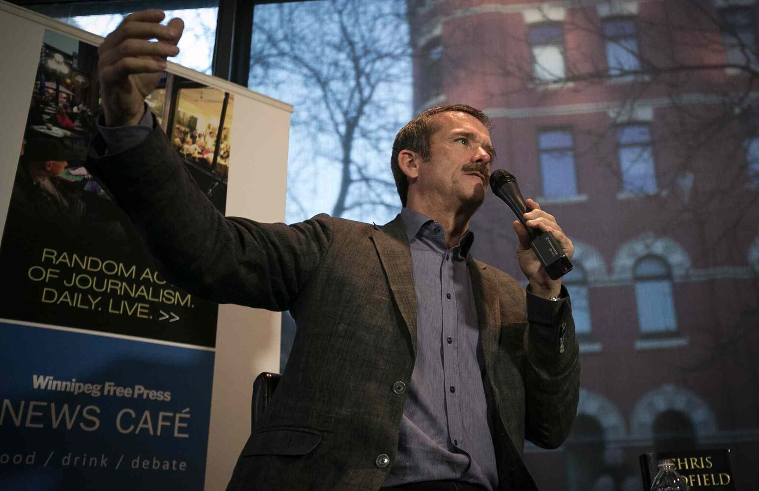 Col. Chris Hadfield explains the intricacies of space flight to a packed Winnipeg Free Press News Café on Wednesday. (Melissa Tait / Winnipeg Free Press)