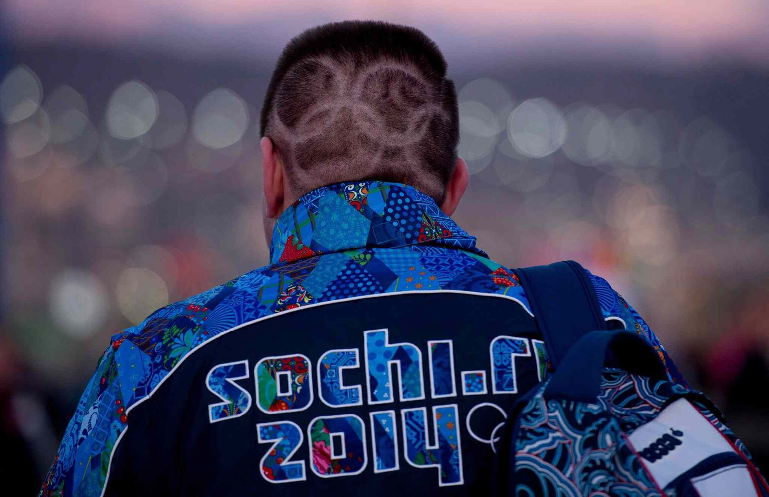 CORRECTS NATIONALITY - A Russian fan with Olympic rings shaved into his hair make his way to the opening ceremonies for the Sochi Winter Olympics Friday February 7, 2014 in Sochi, Russia. THE CANADIAN PRESS/Adrian Wyld